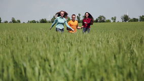 Three friends. A man and two girls holding hands running on the green field. stock video