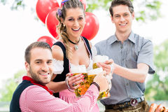 Three friends in Munich Beer garden clinking. Glasses wearing traditional Tracht stock photography