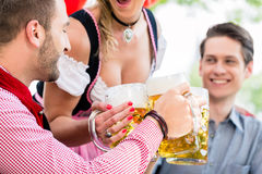 Three friends in Munich Beer garden clinking. Glasses wearing traditional Tracht stock images
