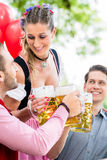 Three friends in Munich Beer garden clinking. Glasses wearing traditional Tracht stock photos
