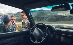Three friends near the car discuss the route in the journey. Travel vacation concept royalty free stock image
