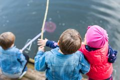 Three friends play fishing on wooden pier near pond. Two toddler boys and one girl at river bank. Children having fun with sticks Stock Photos