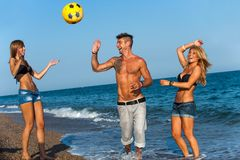 Three friends playing with ball on beach. Stock Photography
