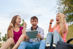 Three friends playing game on tablet pc. They winning again. Stock Image
