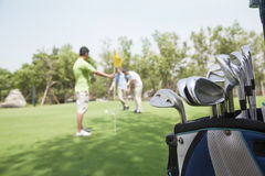 Three friends playing golf on the golf course, focus on the the caddy stock photography