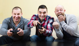 Three friends playing video games Royalty Free Stock Photos