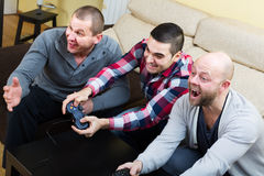 Three friends playing video games Royalty Free Stock Images