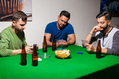 Three friends during poker night. Group of three male friends drinking beer and playing cards for poker night at home Royalty Free Stock Images