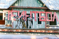 Three friends posing near giant sign with text paintball Stock Photo