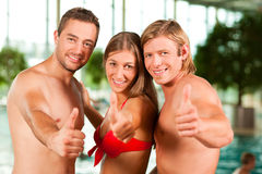 Three friends in public swimming pool Stock Image