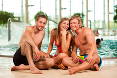 Three friends in public swimming pool Royalty Free Stock Photo