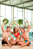Three friends in public swimming pool Stock Photos