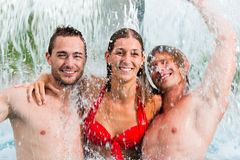 Three friends in public swimming pool Royalty Free Stock Image