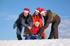 Three friends push girl on sled Royalty Free Stock Photos