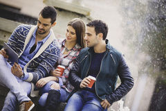 Three friends relaxing with a digital tablet Stock Photography