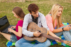 Three friends relaxing and having fun in park. Stock Images