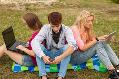 Three friends relaxing and having fun in park. Royalty Free Stock Photos