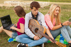 Three friends relaxing and having fun in park. Royalty Free Stock Photography