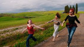 Three friends run along a gravel path in the middle of a green summer field. stock video footage