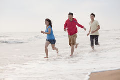 Three friends running on the beach by the waters edge, China Stock Photo