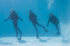 Three friends on scuba training submerged in swimming pool Royalty Free Stock Photos