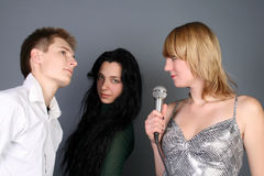 Three friends singing a song. In studio Royalty Free Stock Photos