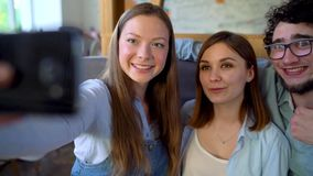 Three friends sit in a cafe, have fun communicating and make selfie. Slow motion. Three smiling friends sit in a cafe, drink juice, have fun communicating and stock footage