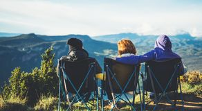 Three friends sit in camping chairs on top of a mountain, travelers enjoy nature and cuddle, tourists look into distance on back. Ground of panoramic landscape stock images