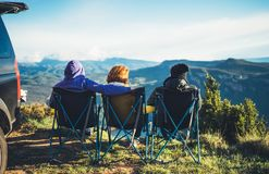 Three friends sit in camping chairs on top of a mountain, travelers enjoy nature and cuddle, tourists look into distance on back. Ground of panoramic landscape royalty free stock image