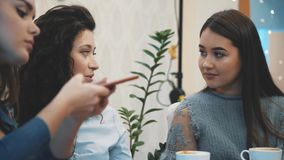 Three friends sitting in a cafe with a smart phone and having a funny conversation. Good girls with long beautiful black. Three friends sitting in a cafe with a stock footage
