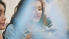 Three friends sitting in a cafe with a smart phone and having a funny conversation. Good girls with long beautiful black. Hair. On the table three cups of stock footage
