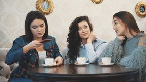 Three friends sitting in a cafe with a smart phone and having a funny conversation. Good girls with long beautiful black. Hair. On the table three cups of stock video