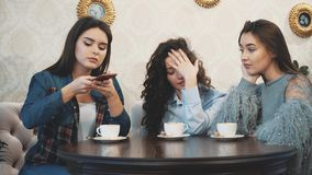 Three friends sitting in a cafe with a smart phone and having a funny conversation. Good girls with long beautiful black. Hair. On the table three cups of stock video footage