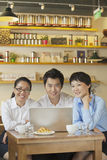 Three friends sitting in coffee shop, looking at camera royalty free stock photography