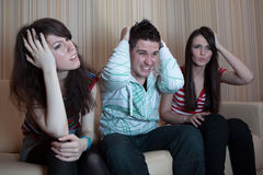 Three friends sitting on the couch. In the living room and watching something ugly on TV Stock Photography