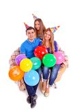 Three friends sitting on a couch with hats and balloons Royalty Free Stock Image