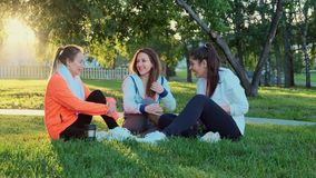 Three friends are sitting on the grass after a morning jog, they laugh and talk.