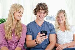 Three friends sitting and looking into the phone Stock Images
