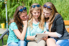 Three friends sitting in park and looking something on tablet Stock Images