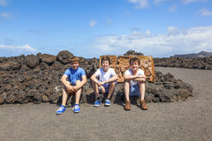 Three friends sitting on a rock and have a rest Stock Photo