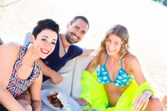 Three friends sitting in sand on beach Royalty Free Stock Images