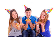 Three friends sitting on a sofa and eating pizza Royalty Free Stock Photo