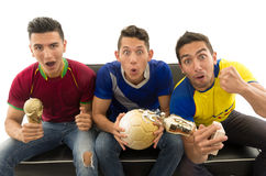 Three friends sitting on sofa wearing sports shirts, holding ball and trophy screaming cheering at camera with royalty free stock images