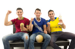 Three friends sitting on sofa wearing sports shirts smiling interacting with camera holding trophy and ball, white Stock Photos