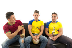 Three friends sitting on sofa wearing sports shirts smiling mocking interacting with each other holding trophy and ball Royalty Free Stock Photo
