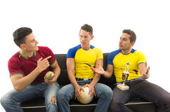 Three friends sitting on sofa wearing sports shirts smiling mocking interacting with each other holding trophy and ball Royalty Free Stock Images