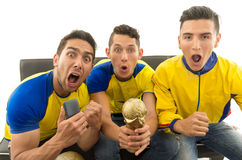 Three friends sitting on sofa wearing yellow sports shirts screaming cheering at camera with enthusiasm, white Stock Photography