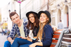Three friends sitting together on the bench. On the beautiful street during summer day time in Europe Royalty Free Stock Photos