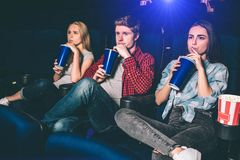 Three friends are sitting together and drinking coke at the same time. They are watching movie. Young people are serious stock image