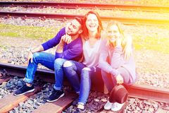 Three friends sitting on train tracks and enjoying the sun stock photo